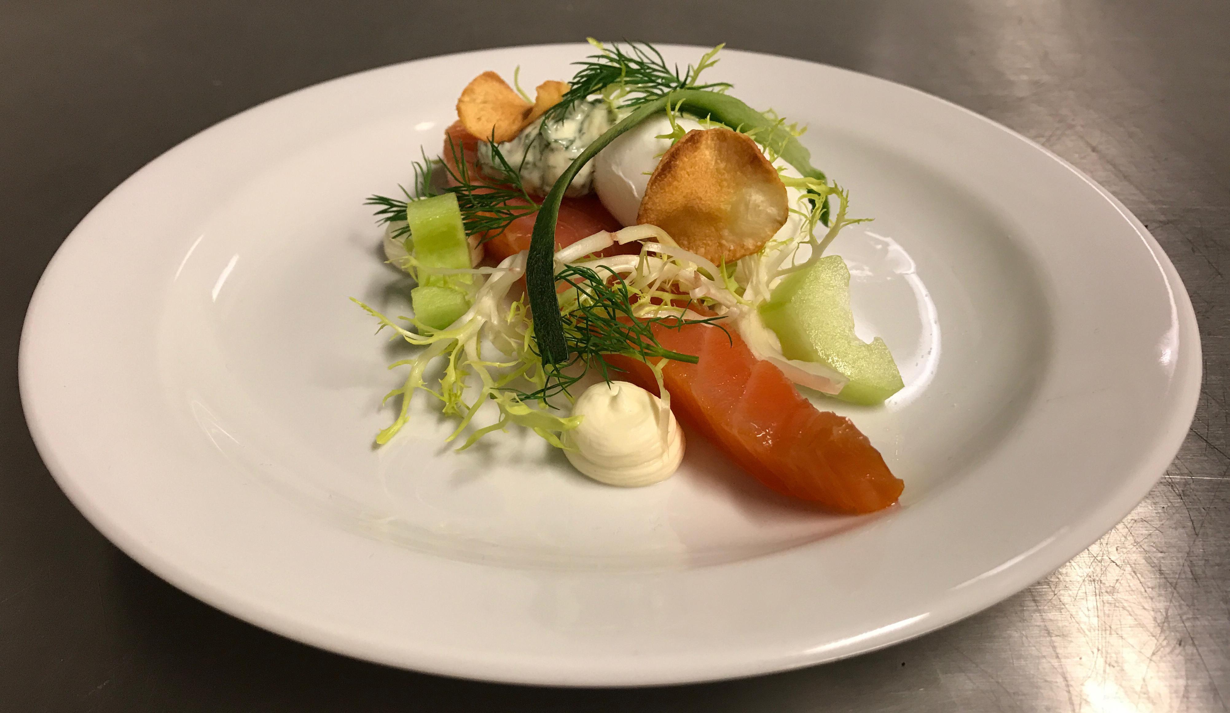 Røget laks med pocheret æg, rygeostecreme, dildmayonnaise, frisée-salat, agurk og havreflager ...